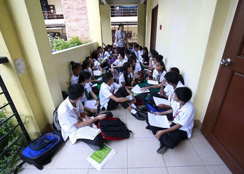دانش آموزان فیلیپینی که به دلیل محدود بودن کلاس ها به همراه معلم خود در راهرو به درس خواندن ادامه می دهند.