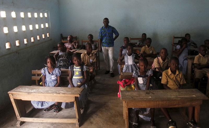 دانش آموزان ابتدایی ساحل عاج به همراه معلم خود.