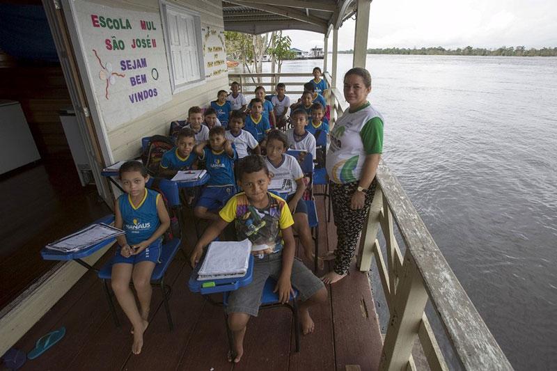 بچه های مدرسه ای شناور که به همراه معلم خود در کنار رودخانه آمازون درس می خوانند. برزیل.