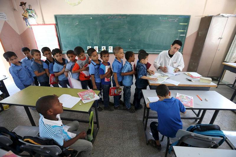 دانش آموزان ابتدایی در حال نشان دادن تکالیف خود به معلم، غزه.